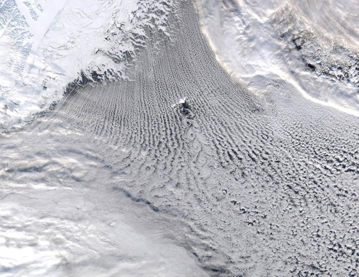 MODIS true-colour satellite image showing linear cloud patterns known as 'cloud streets' over the Greenland and Iceland Seas. These clouds are a signature of the transfer of heat and moisture that warms the atmosphere and cools the ocean resulting in a convective overturning of the water column, a process that plays an important role in the Atlantic Meridional Overturning Circulation. The island of Jan Mayen is in the center of the image and the flow around its topography results in the formation of spiraling cloud patterns known as 'von Karman vortices'. CREDIT Courtesy of GWK Moore