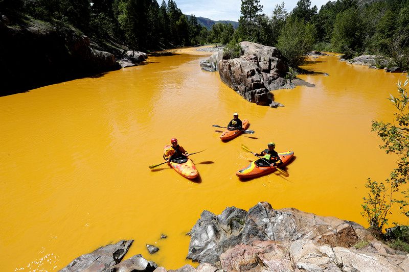 """People kayak in the Animas River near Durango, Colo., Thursday, Aug. 6, 2015, in water colored from a mine waste spill. The U.S. Environmental Protection Agency said that a cleanup team was working with heavy equipment Wednesday to secure an entrance to the Gold King Mine. Workers instead released an estimated 1 million gallons of mine waste into Cement Creek, which flows into the Animas River. (Jerry McBride/The Durango Herald via AP) MANDATORY CREDIT"""