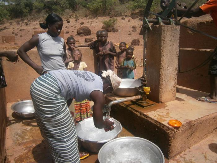 This image shows women collecting water at a well in rural Burkina Faso, West Africa. CREDIT Kathryn Grace
