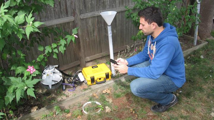 Stephen Decina, Boston University PhD student, measures carbon dioxide being released from the soil using an automated soil carbon dioxide efflux system. The equipment, which is controlled with a smartphone, passes air through an infrared gas analyzer and measures the concentration of carbon dioxide accumulation over time.