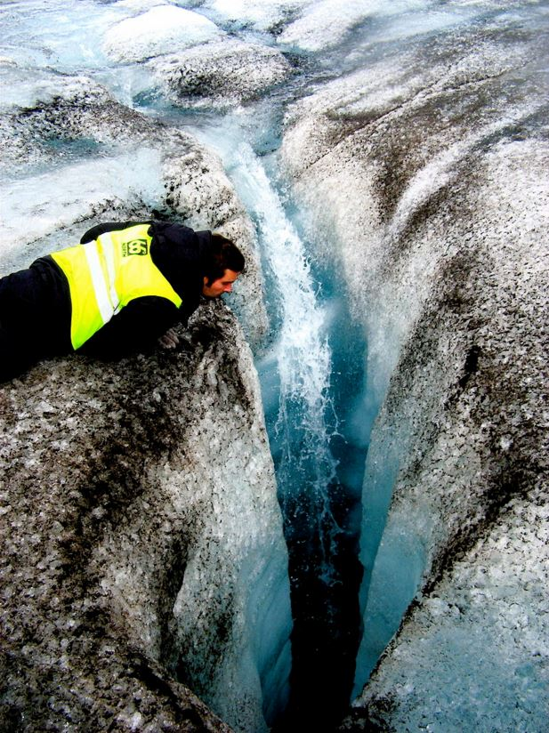 A crevasse created by water drilling a hole tens of meters deep into the glacier ice. A layer of dark cryoconite surrounds it. Langjökull glacier. July 2006. Image: Ville Miettinen from Helsinki, Finland - Crevasse, CC BY 2.0