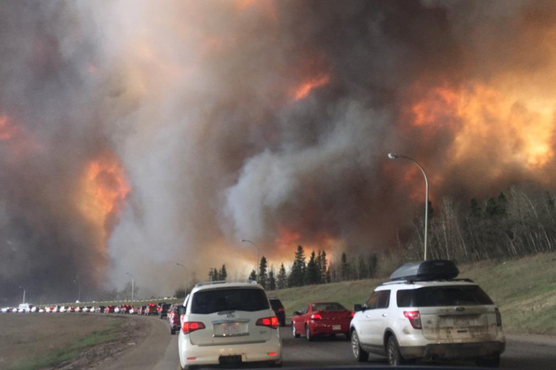 2016 Fort McMurray wildfire. Large flames and heavy smoke surround congested Highway 63 South.