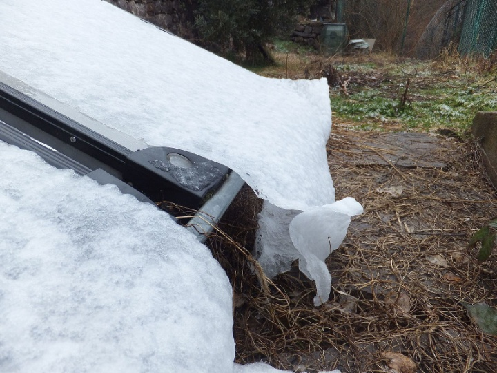 """Snow """"sheets"""" above some solar panels; pushed by the rain, they are sloping down folding themselves like real sheets"""