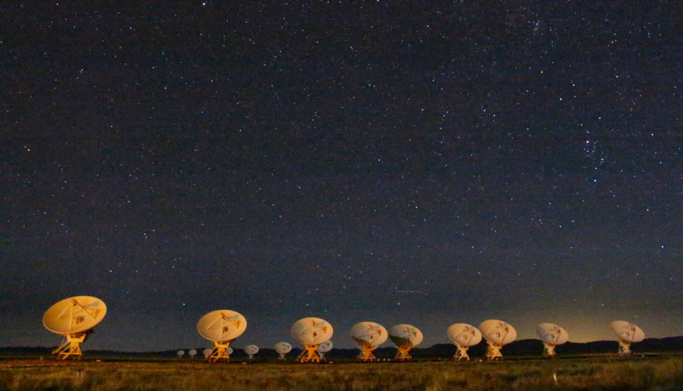 The Very Large Array (VLA) of radio telescopes at night.