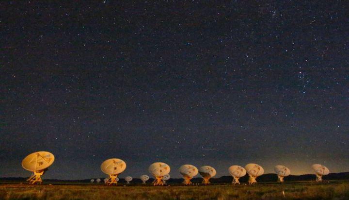 The Very Large Array (VLA) of radio telescopes at night.