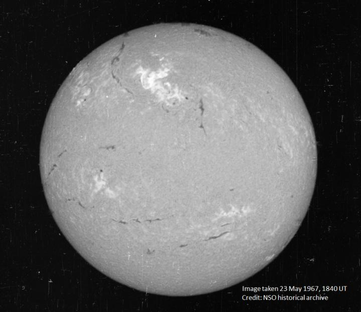 A view of the sun on May 23, 1967, in a narrow visible wavelength of light called Hydrogen-alpha. The bright region in the top center region of brightness shows the area where the large flare occurred. CREDIT National Solar Observatory historical archive.