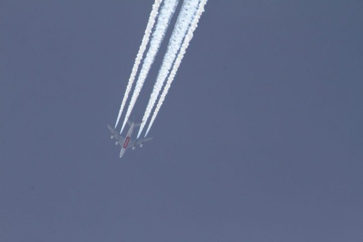 A commercial airliner produces a condensation trail in the skies over California. Mick West