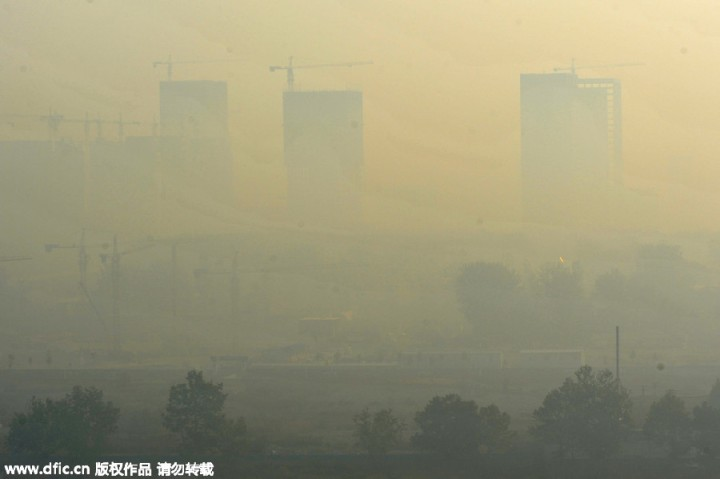 Smog hangs over a construction site in Weifang city, Shandong province, Oct 16. 2015. Air quality went down in many parts of China since Oct 15 and most cities are shrounded by haze. [Photo/IC]