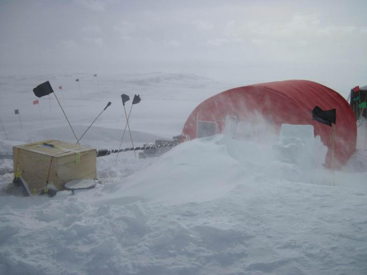 Blustery conditions at the West Antarctica ice sheet divide, a ridge where a 3.4-kilometer borehole was drilled to acquire ice cores. The tent protected the equipment and scientists as they measured temperatures down the borehole in 2011 and 2014. CREDIT US Geological Survey